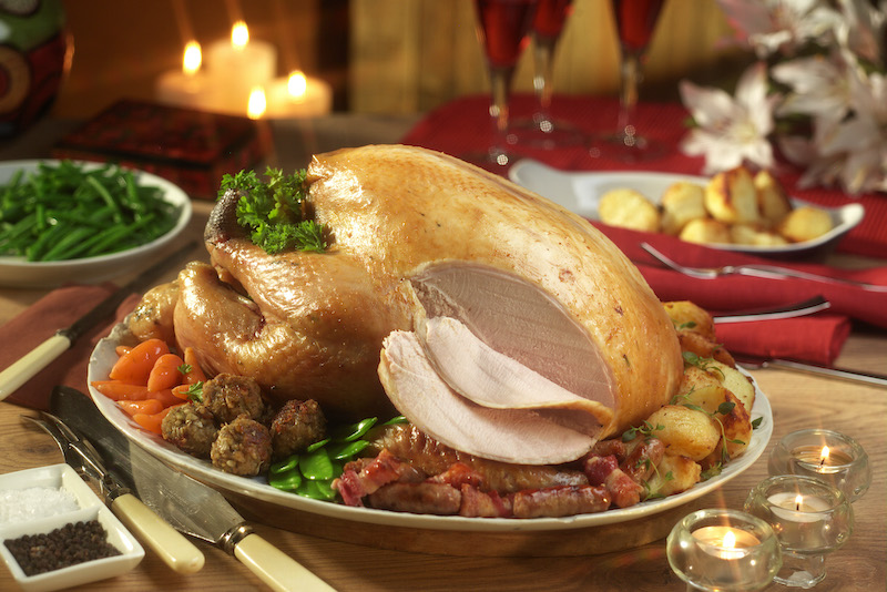 A sliced Norfolk Bronze turkey served in a beautiful Christmas setting with all the trimmings